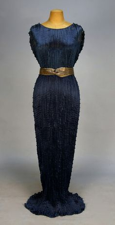 FORTUNY DELPHOS GOWN with SASH and ORIGINAL BOX, c. 1930. Vibrant blue silk trimmed at the shoulder, armhole and side with black and white striped Murano glass beads, silver stenciled blue silk twisted and looped sash with hook & eye closures, selvedge stamped in red
