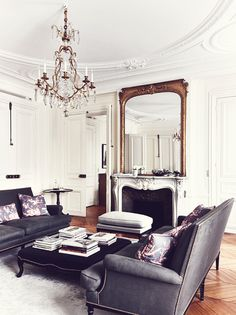 Adore this room! The black sofas, the symmetry, the chandelier and the fireplace are all gorgeous!