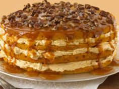Luscious Four-Layer Pumpkin Cake - with a yummy cream cheese / cool whip filling between layers and topped with drizzled caramel and chopped nuts!!!