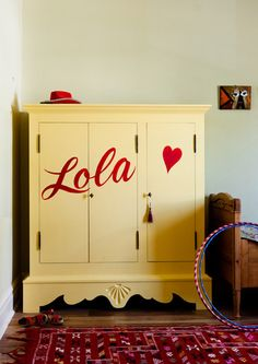 awesome personal touch on a hand-me-down piece of furniture - little girl's name and a simple shape boldly painted across the front of a wardrobe