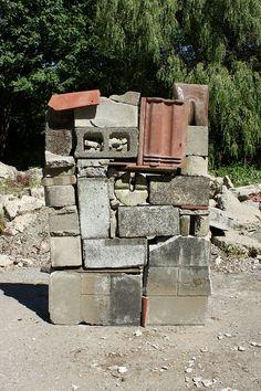 Stacked cinder blocks, concrete, clay shingles, wood, shovel