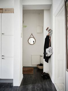 Hallway with black floors in a calm Swedish home. Stadshem.