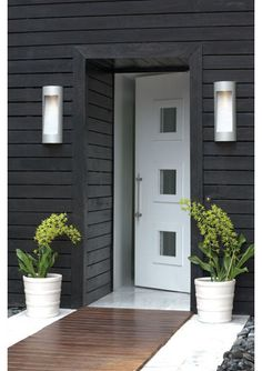 Create a modern clean entrance with black and white. Black cladding and cobbles, a white door, tiles and pots. The dark wood floor draws you in and warms up the whole effect, stunning!
