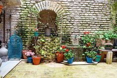 Unique experience in Seville/ Sevilla (Spain). Old fashioned rustic antique austere courtyard patio in stone brick house full of bright colorful red green flowers and mold moldy walls and water well. Rusted metal water bucket hanging above handmade water well. Brick marble DIY handmade floor/ flooring. Moroccan/ Arabic/ Southern Spain style pot and vessel ,art exterior/ interior with amazing atmosphere with bright light picturesque large space. Ideas and design by juancarloscoquerel.com