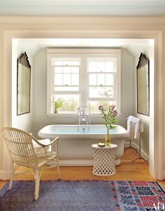 Moroccan mirrors flank a tub in the master bath of a Hamptons home, creating perfect symmetry.
