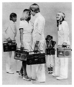First I wondered what cheesy Eurodisco they were probably listening to. Then I wondered if long haired 70's tennis player stoner looking dude on the left is totally oblivious to both the chick sitting down and and the guy on the right are totally giving him googly eyes.