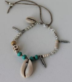 item #B058 Sugar skull- is a bracelet made with a white skull bead, cowrie shells, glass beads, three silver leaf charms set with silver plated beads on natural cord.