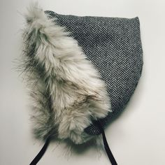 This luxe winter bonnet is fully lined in a beautifully soft faux fur and trimmed with velvet.