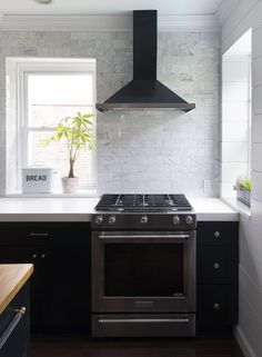 Black kitchen with full wall of white marble tile black range hood with stainless stove- Dessign Manifest
