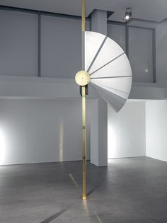 A fan that opens around a brass disk gradually unfolds over the space of five minutes, forming a full circle before snapping back shut.