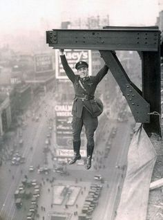 A man hangs from a skyscraper in New York City.