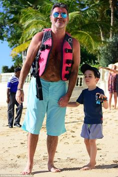 Father-son time: Music mogul Simon Cowell showcased his taut physique as he enjoyed a envi...