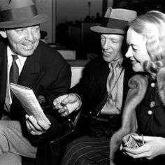 Clark Gable and fourth wife Sylvia Ashley check out who's running in the horse race with Fred Astaire.