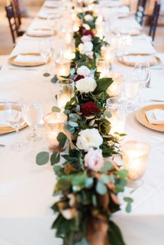 Wedding table covered in garland and roses: http://www.stylemepretty.com/2016/09/02/classichouston-wedding-with-pop-of-red/ Photography: Dana Fernandez - http://www.danafernandezphotography.com/