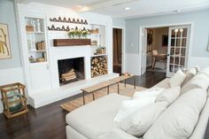 The updated family room is bright and airy with a painted white fireplace, recessed lighting, wainscoting, and warm wood decorative accents, as seen on Fixer Upper. French doors lead into the office. NOTE the easy to make bench/coffee table. Farmhouse Fireplace Mantels, White Fireplace, Brick Fireplace, Living Room With Fireplace, New Living Room, Living Room Decor, Fireplaces, Off Center Fireplace, Office With Fireplace
