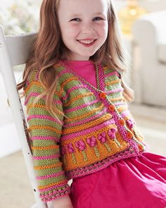 Little girls look absolutely darling in the cardigan, featuring colorful stripes and bobble-topped flowers! Shown in Bernat Satin. #knitting