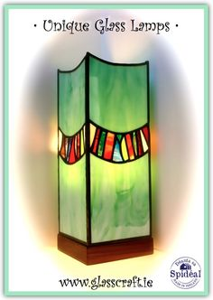 Stained glass unique lamp with design on all four panels, attached to a hand carved walnut wooden base