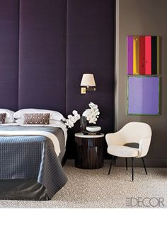 In a bedroom designed by Iain Halliday, a Saarinen armchair and custom bedside table are paired with a bed dressed in Frette linens; paintings by Anselm Reyle hang on walls painted in Benjamin Moore's Eagle Rock, the swing-arm sconces are from Hinson Lighting, and the carpet is by ABC Carpet & Home.