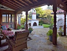 Backyard porch of Spanish Mediterranean Home with built in fireplace