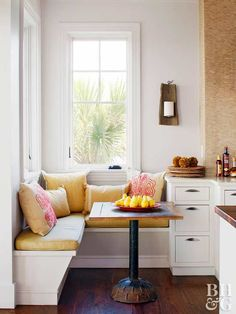 This tiny L-shape banquette tucks neatly into a corner of this cozy cottage kitchen. Topped by windows, the bench provides a sunny spot to enjoy a relaxing breakfast or the morning paper. A small table fits snugly against the bench without interrupting traffic flow around the nearby kitchen island.