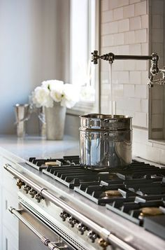Gorgeous stainless steel stove with a great feature with a faucet to fill pots on the stove. Beautiful other design details including the pop of white flowers