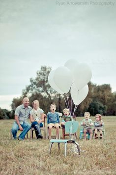 Photo of family waiting for empty chair to be filled by child who is joining their family through adoption.
