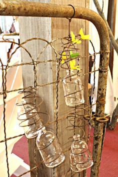 Common Ground: Spring Open House at Leola's Vintage Home and Garden-glass bottles wrapped in wire hanging on garden fence-cute!