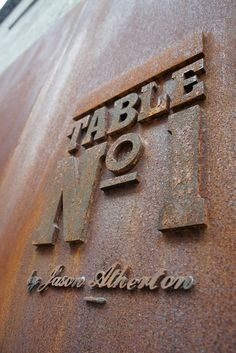 Blocky waterjet or laser cut lettering contrasting with a script font plug welded to a metal plate: