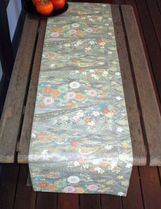 $80.00 Japanese Vintage Silk Fukuro Obi Table Runner.  This has been created from a vintage (circa 1980's) silk fukuro Obi. It has a design featuring chrysanthemums, sakura blossoms with stream and wave motifs. It is embellished with lots of gold and silver foil threads on a sage green background.