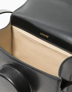 From Lemaire, a minimalist camera bag in Black. Featuring a cast leather construction, adjustable shoulder strap with brass peg closure, main compartment with flap and magnetic closure, contrasting leather interior, interior wall pocket, gold debossed Lem