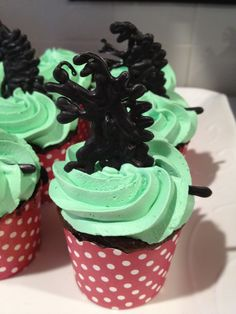 Godzilla cupcakes, for Isi's BirthDAY, printed a silouhette from the internet and placed it under acetate paper(cake dec store) and piped it with black wilton melts. refrigerated and store them till the day of the party  in a tupperware container. place them in cupcakes. My daughter approved it!