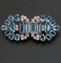AN AQUAMARINE AND DIAMOND BROOCH, BY CARTIER  Designed as a central aquamarine five-stone convex panel within diamond scalloped borders to the oval and triangular-cut aquamarine arrow-shaped terminals, circa 1935, 5.5 cm. wide Signed Cartier, London, no. 3965