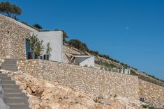The holiday house is located on the highest point of Santorini Island, on 'Prophet Ilias' mountainside. The building faces to the. Concrete Siding, Stone Siding, Concrete Walls, Santorini Holidays, Triangle House, Mediterranean Plants, Mountain Pictures, Santorini Island, Outdoor Pool