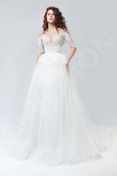 This exquisite wedding gown with a hint of English style will put your femininity and grace on a pedestal.  The short corset with mid-length sleeves highlights your perfect posture, and the lace overlay adds an unparalleled charm. The sheer-insert back with a trail of buttons is alluring, and the voluminous skirt with a peplum detail is light yet majestic.  Allow your beauty to bloom like a flower in the spring air in this enchanting gown.  *The price doesn't include accessories.