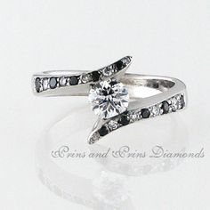 The centre stone is round brilliant cut diamond tension set in a white gold with alternating black and white round cut diamonds on the shank White Gold, Black And White, Black Diamonds, Round Cut Diamond, Shank, Diamond Rings, Centre, Stones, Fancy