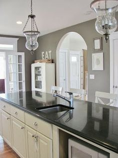 Gray walls in kitchen with black granite and white cabinets. Love the light fixtures.