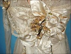Close up of the ecru satin bow-like 'bloom', liberally trimmed with wax orange blossoms ~ placed off center on the bodice, like a giant corsage.
