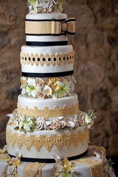 heavily detailed wedding cake in gold lace and black ribbon wiht pistachio floral accents