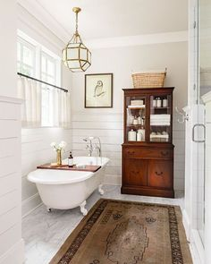 This weekend sales picks are up on Beckiowens.com! Freestanding tub, vintage rug, shiplap + Morris lantern combo is Bathroom via @countrylivingmag