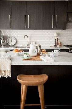 Dark Cabinets With White Counters And Backsplash On