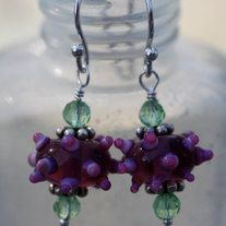 Beautiful raspberry lamp work glass beads with soft lavender and pink bumpies. Topped with bali silver spacers and Chinese crystals. Sterling silver head pin and ear wire. 1 /12 inches from top of ear wire to bottom of earring. Comes wrapped in tissue in a gift bag ready for gift giving!