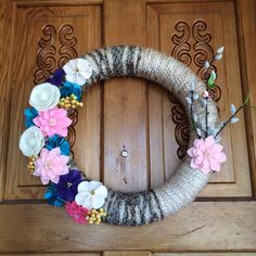 Diy yarn wreath for spring with felt flowers and branches with small bird