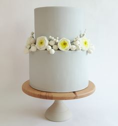 Pale grey two tier wedding cake with sugar ranunculus and berry details by Claire Owen Cakes