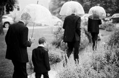 Groomsmen and ring bearer walking through a garden in the rain prior to a wedding at the Chautauqua Community House in Boulder, CO.