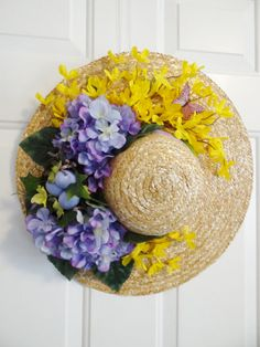Spring wreath on straw hat with purple hydrangeas and yellow forsythia flowers and birds nest