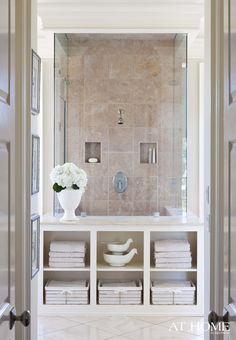 His and hers closets line the hallway connecting the master bath with the bedroom. The glass-walled shower is a focal point when entering the space; designer Susan Latta inserted a built-in cabinet to break up the expanse of glass and add storage.