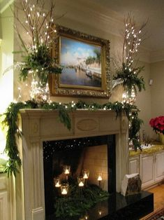 Lights in the gold and silver hurricane globes are topped with red dogwood branches,christmas greens and candles in the fireplace - Decor Collage Ideas