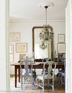 love this dinning room. Wall hangings, chandelier, and different color chairs