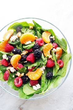 Berry Orange Spinach Salad mixed in a large bowl, which includes raspberries, blackberries, and mandarin oranges.