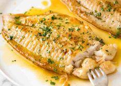 Close up photo of Crispy Pan Fried Fish with Lemon Butter Sauce and a sprinkle of parsley on a white plate.